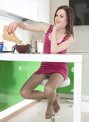 Whitney loves cereal and wears stockings at the table to keep warm. She is done and wants to be naked, so she strips off the stockings and lingerie to be naked. She climbs on the table and shows off her body.